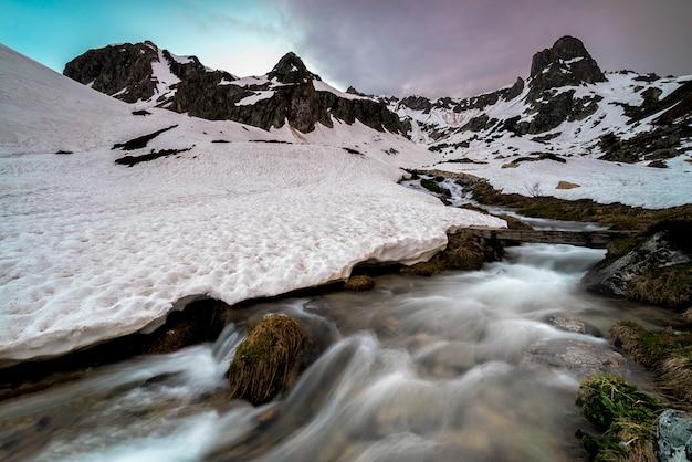 Besneeuwde rivier met bergen in de alpen
