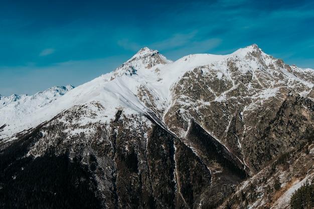 Besneeuwde rotsachtige toppen van bergen bij zonnig weer. de bergen van dombai sluiten omhoog.