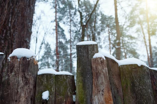 Besneeuwde rustieke hek op het platteland. de sneeuw schittert in de zon.