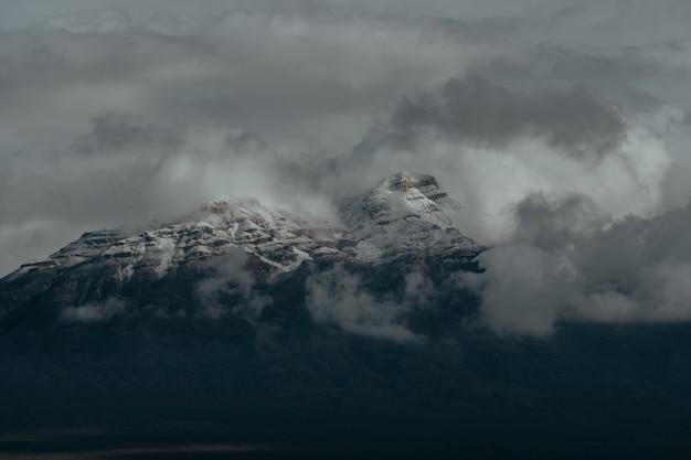 Besneeuwde toppen van de bergen onder de donkere bewolkte hemel