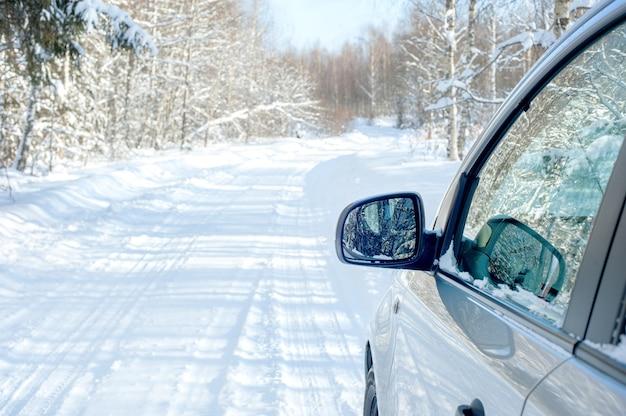 Besneeuwde weg. kant van een auto met een spiegel. besneeuwd bos in de middag