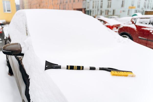 Besneeuwde winter. close-up van de auto met de speciale borstel op de motorkap. apparaat voor het reinigen van sneeuw uit het autoconcept. stock foto