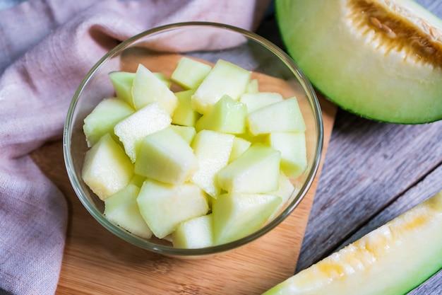 Besnoeiing van verse zoete groene meloen in komglas op de houten lijst. fruit of gezondheidszorg concept.