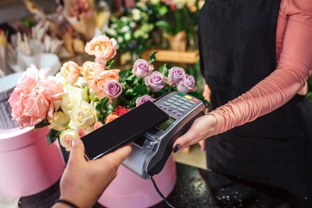 Besnoeiingsmening van de telefoon van de mensenholding boven therminal geld. er staan veel bloemen en planten achter.