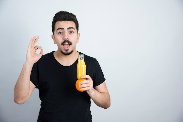 Besnorde man met oranje fruit en glazen fles sap doet ok teken.