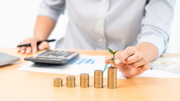 Bespaar geld en investeringen concept, business accountant vrouw stapelen munten in toenemende kolommen stapel voor budget achter bureau met grafieken grafiek focus op geld.