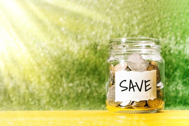 Bespaar geld, munten in glazen pot voor geldbesparende financiële concept
