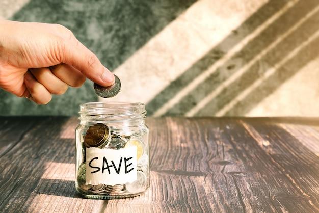 Bespaar geld, vrouw zet munten in glazen pot voor geldbesparende financiële concept