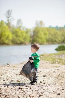 Bespaar milieuconcept, een kleine jongen die afval en plastic flessen op het strand verzamelt om in de prullenbak gedumpt te worden.
