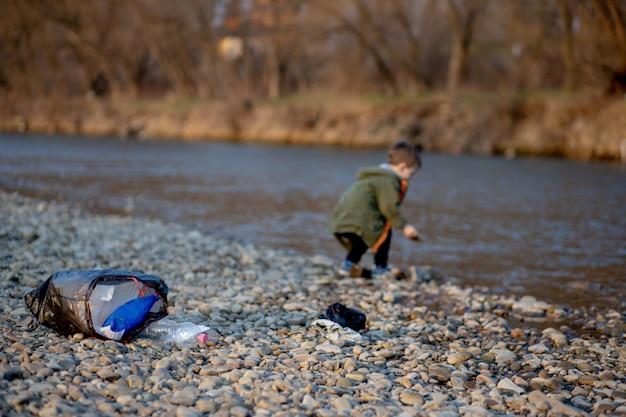 Bespaar milieuconcept, een kleine jongen die afval en plastic flessen op het strand verzamelt om in de prullenbak gedumpt te worden