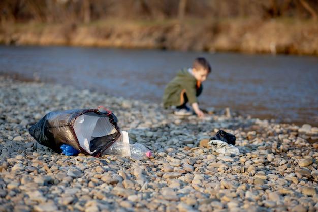 Bespaar milieuconcept, kleine jongen die afval en plastic flessen op het strand verzamelt om in de prullenbak gedumpt te worden