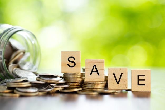 Bespaar woord op geldmunten met munten in een glazen pot. bedrijf. geld besparen voor de toekomst