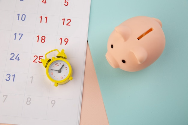 Besparingen concept. spaarvarken en wekker met kalender op kleurrijke achtergrond.