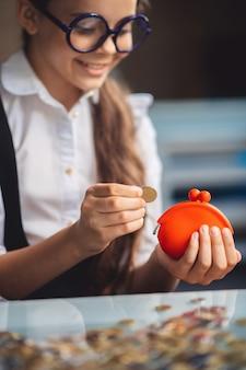 Besparingen. meisje dat in oogglazen haar spaargeld telt en tevreden kijkt
