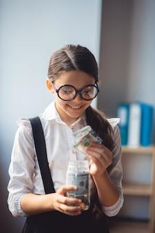 Besparingen. meisje in wit overhemd geld steken in een pot en glimlachen
