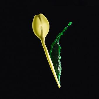 Bespattende gele en groene verf die bloemknop over donkere achtergrond vormen