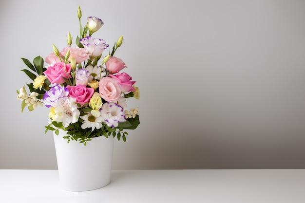 Bespotten boeket rozen, madeliefjes, lisianthus, chrysanten, ongeopende knoppen in een witte kartonnen doos