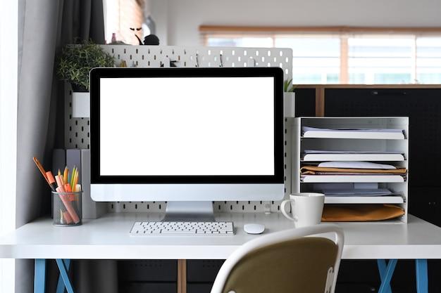 Bespotten computer met leeg scherm op wit bureau in kantoor aan huis.
