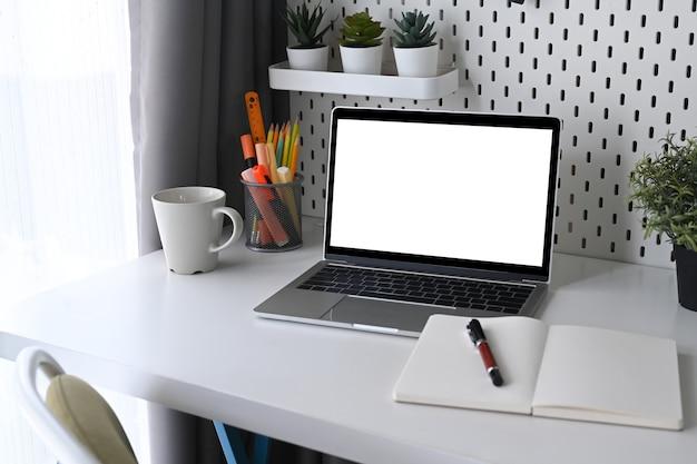 Bespotten computerlaptop, kamerplant en notitieboekje op bureau aan huis.