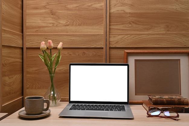 Bespotten computerlaptop, koffiekopje, bloemen en leeg fotolijstje op houten bureau.