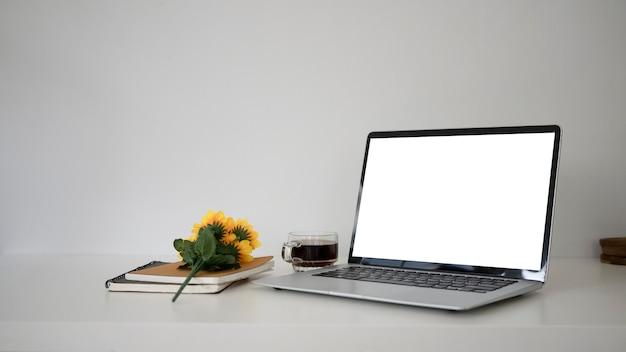 Bespotten computerlaptop met leeg scherm, koffiekopje, notitieboekje op witte tafel.