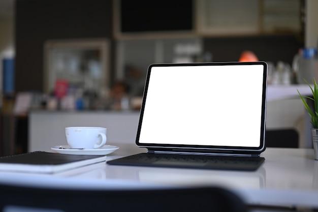 Bespotten computertablet met leeg scherm, notebook en koffiekopje op witte tafel in de keukenkamer.