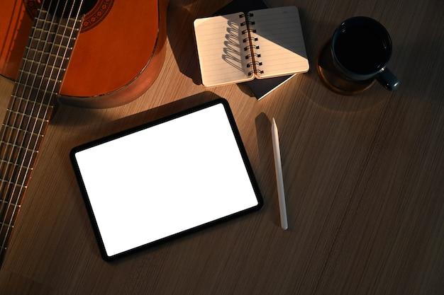 Bespotten digitale tablet, notebook, koffiekopje en gitaar op houten vloer in de woonkamer.