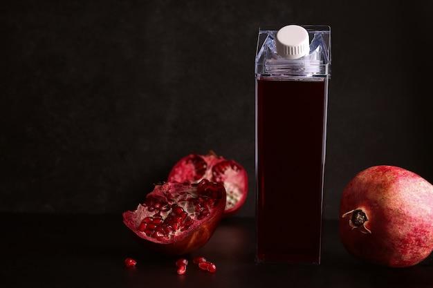 Bespotten flessen met granaatappelsap op een zwarte achtergrond. het volgende ingrediënt is verse granaatappel. kopieer ruimte