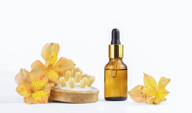 Bespotten glazen druppelflesje en natuurlijke houten massageborstel en bloemen. concept - massage, cosmetologie, cosmetica, schoonheidsconcept.