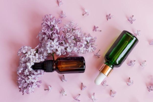 Bespotten glazen druppelflesjes op een roze achtergrond met lila bloemen. merkloos cosmetisch pipet serum.
