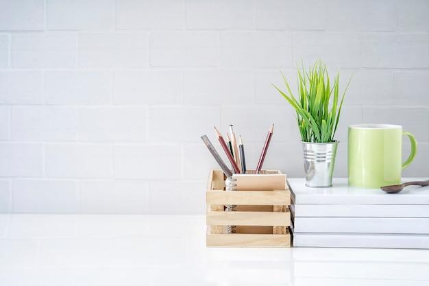 Bespotten houten doos met potlood, kamerplant en groene mok op boek op witte tafel