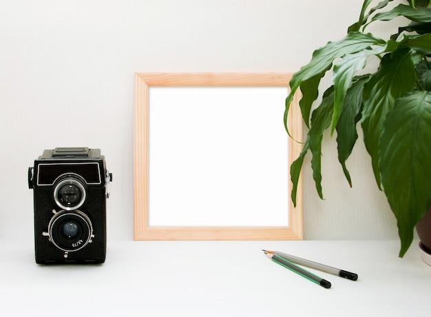 Bespotten houten frame, oude camera, plant en potloden.