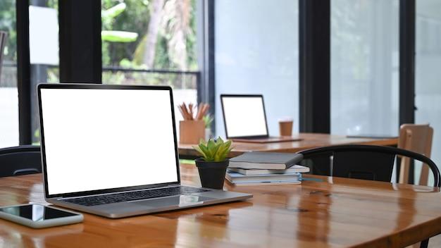 Bespotten laptop en mobiele telefoon op houten tafel in vergaderruimte.