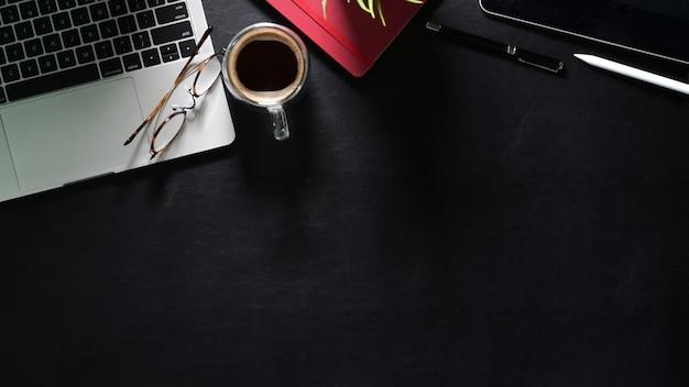 Bespotten laptop met kantoorbenodigdheden op donkere bureau en kopie ruimte