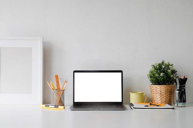 Bespotten laptop op werk ruimte met mok koffie, plat en fotolijst kopie ruimte kantoor.