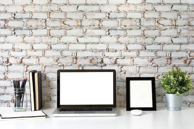 Bespotten laptop op werk ruimte met mok koffie, plat en fotolijst office-tafel.
