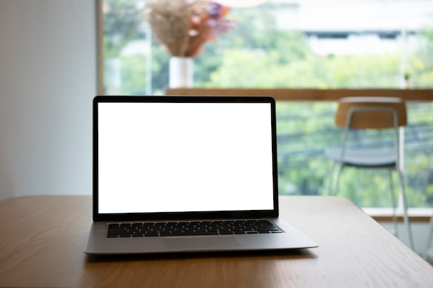 Bespotten laptopcomputer met wit scherm op houten tafel in café.