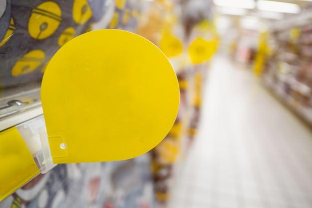 Bespotten lege gele kortingsmarkering op de productenplanken in supermarkt