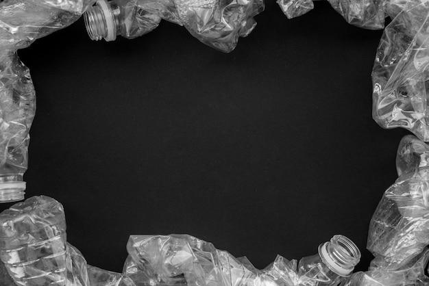 Bespotten met het thema milieubescherming. samengeperste plastic flessen op een zwarte achtergrond.