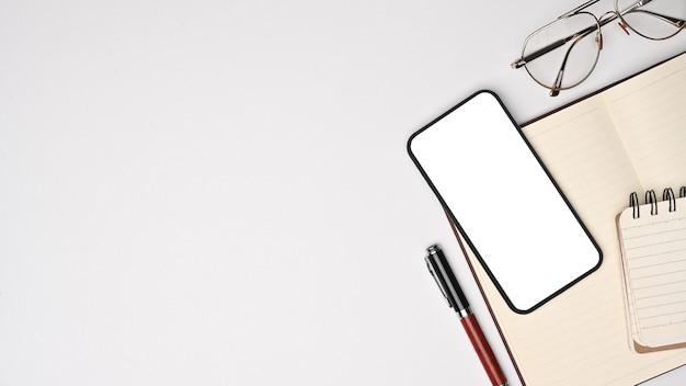 Bespotten slimme telefoon met leeg scherm, notebook en bril op wit bureau.