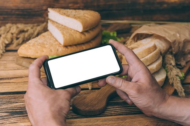 Bespotten smartphone in de hand op ruimte met vers brood op een houten ruimte.