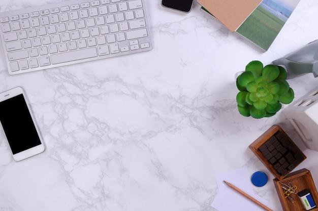 Bespotten smartphone met kajboard en kantoorbenodigdheden op marmeren achtergrond