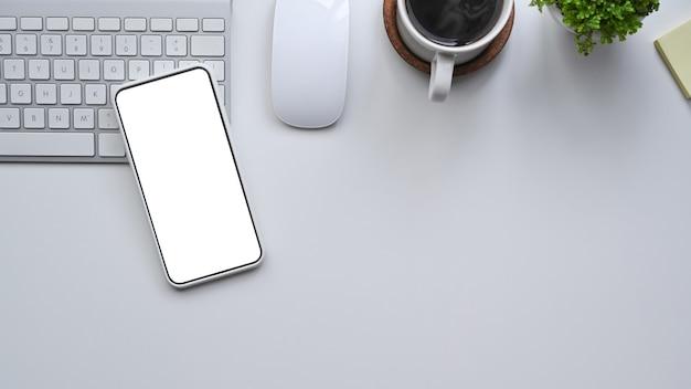 Bespotten smartphone met leeg display op wit bureau.
