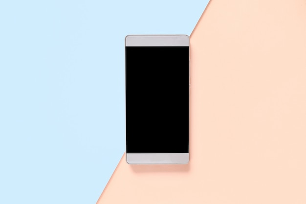 Bespotten smartphone op een blauw oranje pastel gekleurde achtergrond. ontwerp voor reclame