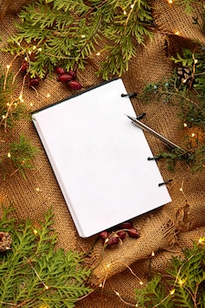 Bespotten van bovenaanzicht op notebook met feestelijke sparren en jute achtergrond