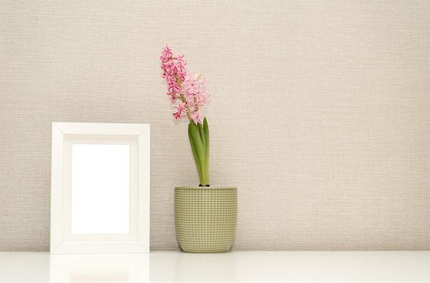Bespotten van een leeg fotolijstje op een witte tafelpot met roze hyacint