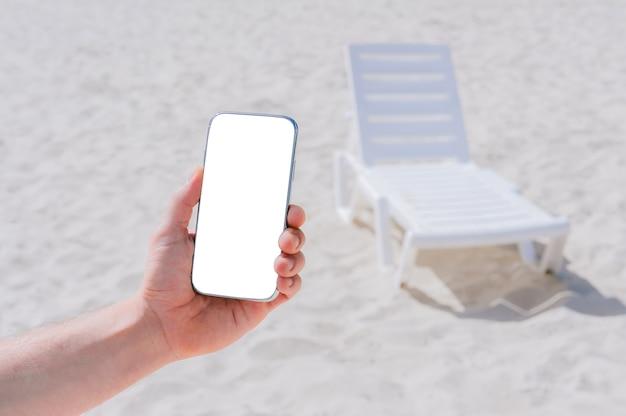Bespotten van een smartphone in een mannenhand. tegen de achtergrond van het strand en de ligstoelen.