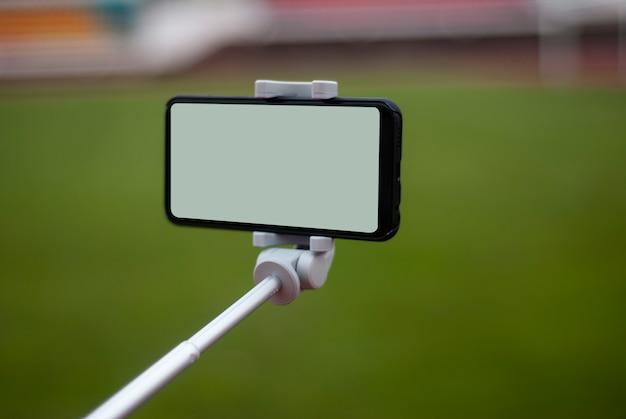 Bespotten van een zwarte smartphone met een selfiestick