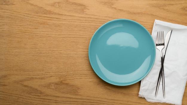 Bespotten van keramische plaat, vork en tafelmes op wit servet, bovenaanzicht, schone plaat, lege keramische schaal, tafel instelling achtergrond