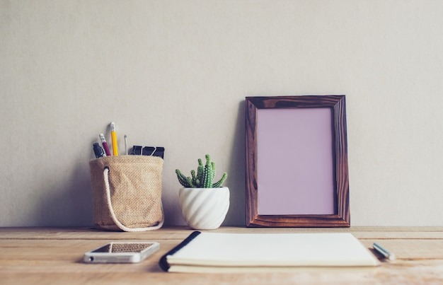 Bespotten van leeg fotokader met cactusbloem op bureau.